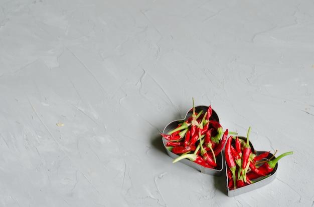 Cœurs en aluminium remplis de petits poivrons frisquets sur fond gris. concept d'amour et de passion
