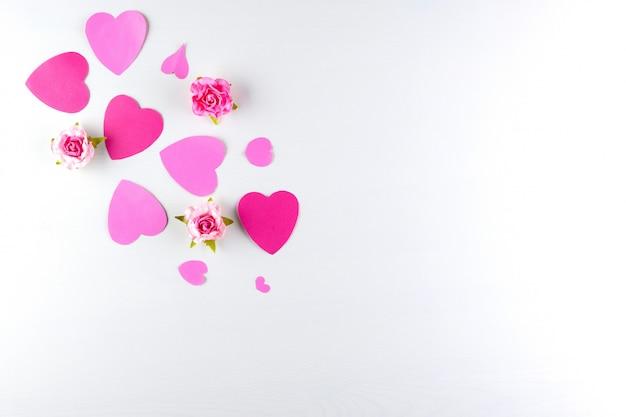 Coeurs d'amour à la main rose isolés sur fond de texture en bois blanc
