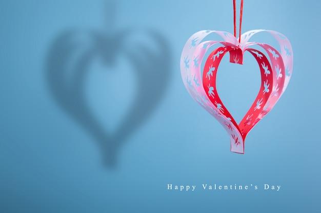 Coeurs avec des anges à la main avec une ombre sur un fond bleu, une bonne carte de félicitations.