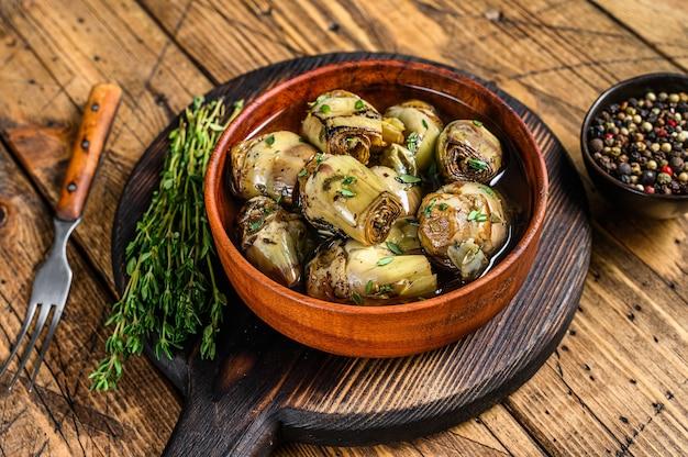 Coeurs d'artichaut marinés à l'huile d'olive. fond en bois. vue de dessus.