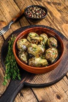 Coeurs d'artichaut marinés à l'huile d'olive. table en bois. vue de dessus.