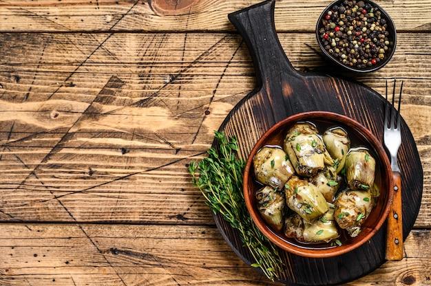 Coeurs d'artichauts marinés à l'huile d'olive. fond en bois. vue de dessus. espace de copie.