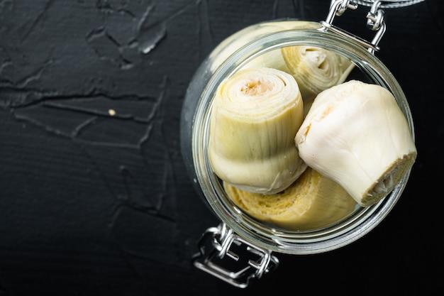 Coeurs d'artichauts marinés à l'huile d'olive, sur fond texturé noir, vue de dessus avec un espace réservé au texte