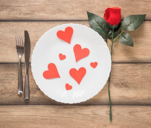 Coeurs sur assiette entre coutellerie et fleur