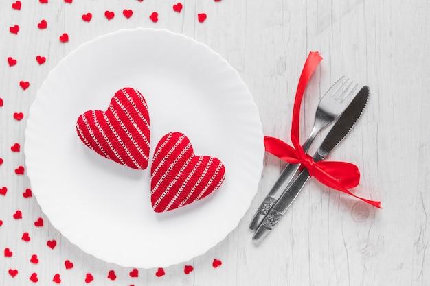 Coeurs sur une assiette près de la coutellerie