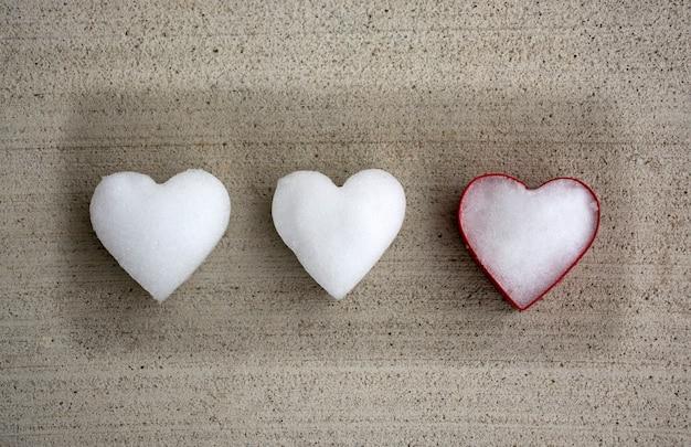 Coeurs blancs faits de neige avec un emporte-pièce de couleur rouge portant sur fond gris