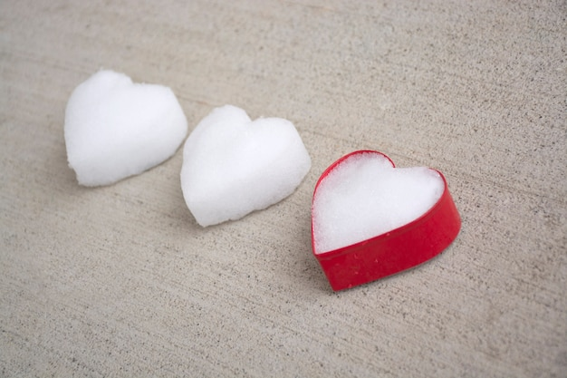 Coeurs blancs faits de neige portant sur du béton