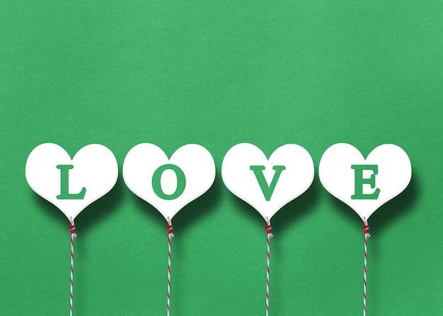 Coeurs blancs sur un fond de papier vert.