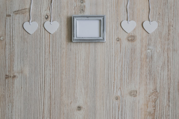 Coeurs blancs suspendus sur une corde et un cadre photo vide dans le milieu