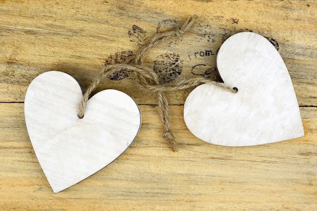 Coeurs en bois blancs sur une surface en bois