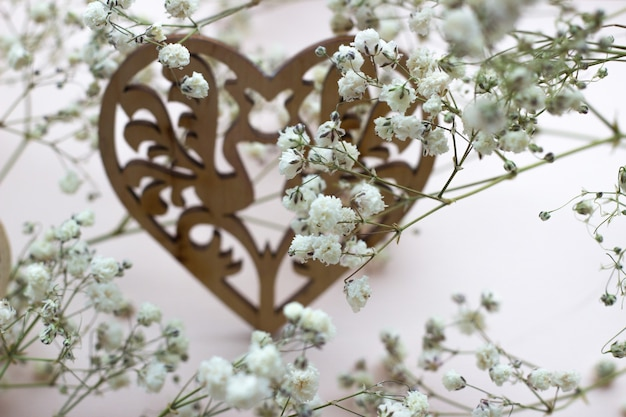 Coeurs en bois et fleurs blanches sur fond clair