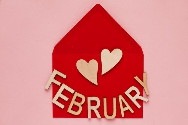 Coeurs en bois et le mot des lettres février dans une enveloppe en papier rouge