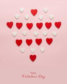 Coeurs en bois rouges sur fond rose pastel