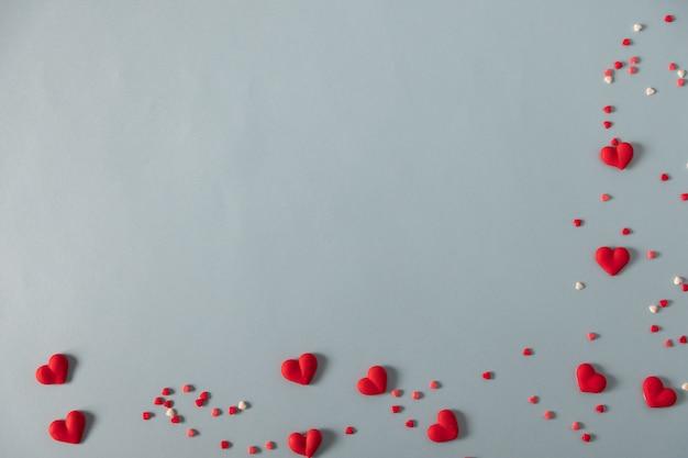 Coeurs de bonbons rouges sur la table bleu pastel
