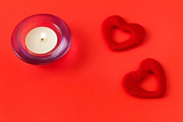 Coeurs et bougies sur fond rouge