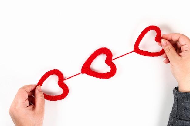 Coeurs de bricolage faits à la main rouge en carton, fil sur fond blanc.