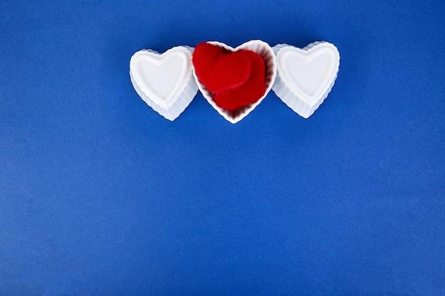 Coeurs en céramique blanche avec des coeurs en peluche rouge sur fond de couleur tendance bleue. composition à plat. concept romantique, saint valentin. l'amour. copiez l'espace.