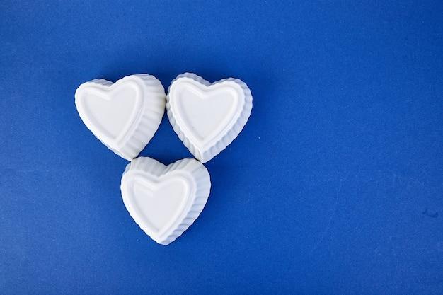 Coeurs en céramique blanche sur fond de couleur tendance bleue. composition à plat. concept romantique, saint valentin. l'amour. copiez l'espace.