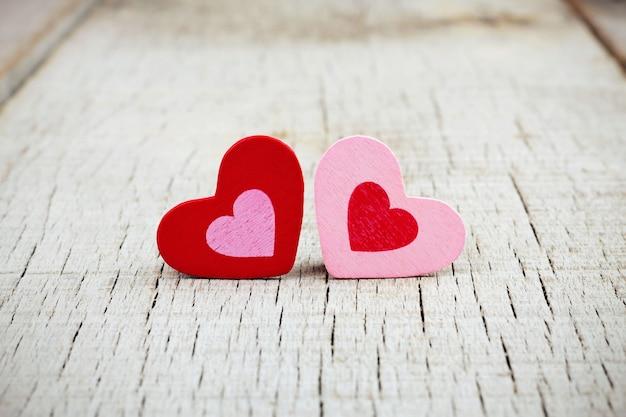 Coeurs de colorés sur fond de bois.