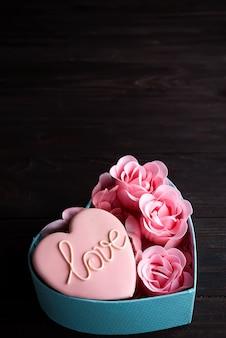 Coeurs cookies dans une boîte coeur bleue avec rose sur fond en bois foncé, espace copie