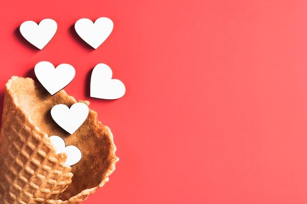 Coeurs dans un cornet de crème glacée vide sur un bacground rouge.