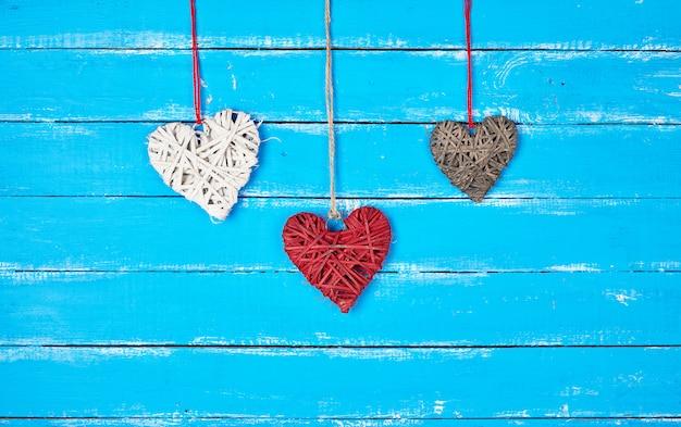 Coeurs décoratifs en osier rouge, blanc et gris suspendus à une corde