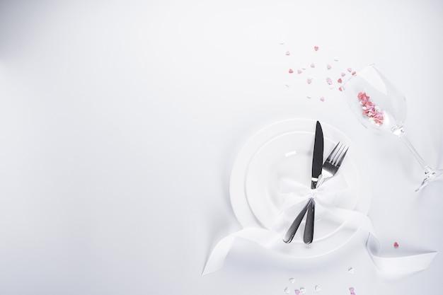 Coeurs doux dans un verre avec des couverts et un ruban blanc sur fond blanc, avec place pour le texte. la saint-valentin. concept d'amour.