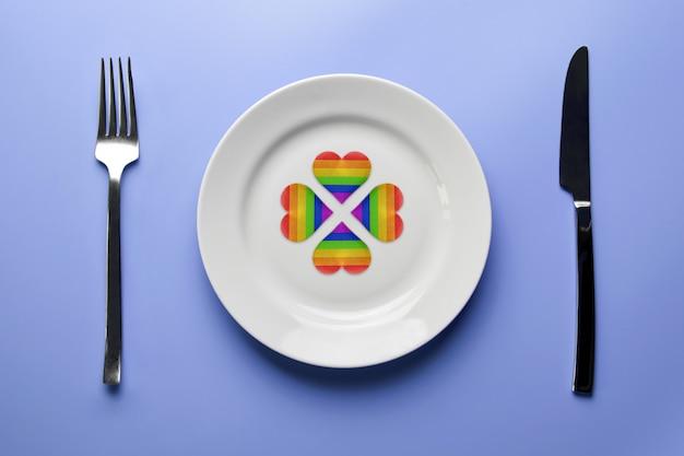 Coeurs de drapeau lgbt sur assiette avec couverts