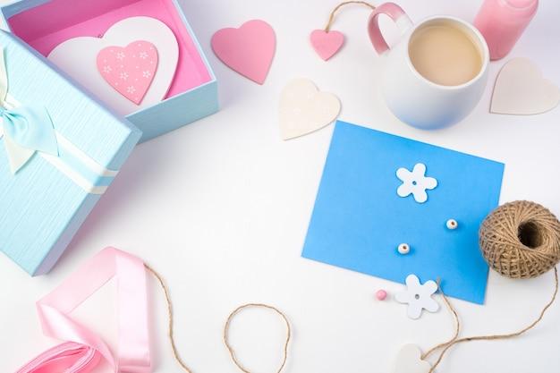 Coeurs, enveloppe bleue et coffret cadeau sur fond clair.
