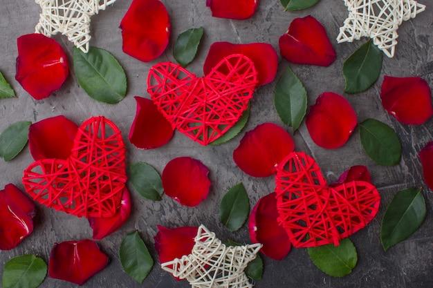 Coeurs et étoiles sur pétales de rose et feuilles vertes