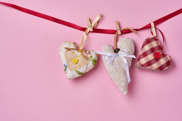 Coeurs faits à la main sur ruban rouge devant le mur rose. carte de voeux saint valentin. vue de dessus.