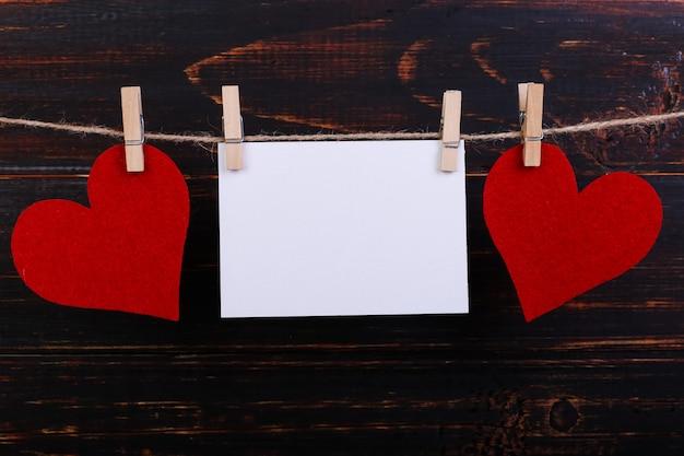 Coeurs en feutre rouge faits à la main et papier blanc suspendu à une corde avec des pinces à linge
