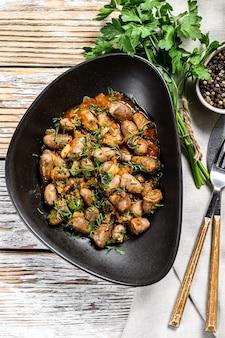Coeurs de foie de poulet cuits dans une assiette. fond en bois blanc. vue de dessus.