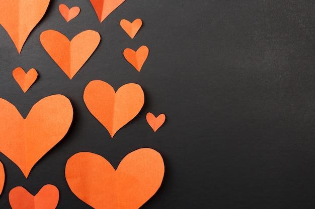 Coeurs sur fond noir avec espace copie. coeurs de papier rouge.