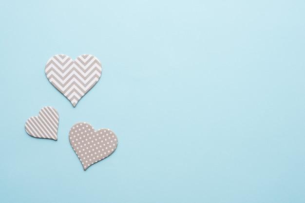 Coeurs gris avec des motifs sur fond bleu pour la saint-valentin