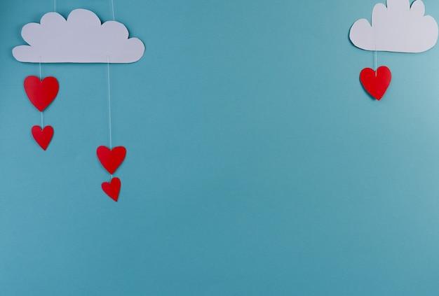 Coeurs et nuages en papier blanc sur fond bleu. abstrait avec des figures découpées en papier. saint valentin, fête des mères, cartes de voeux d'anniversaire, invitation, concept de célébration