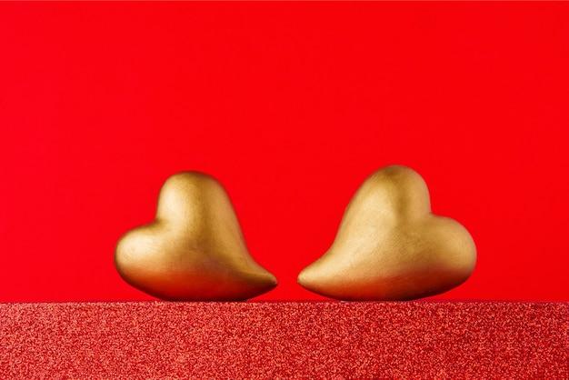 Coeurs d'or sur un podium rouge avec espace de copie. concept de célébration de la saint-valentin