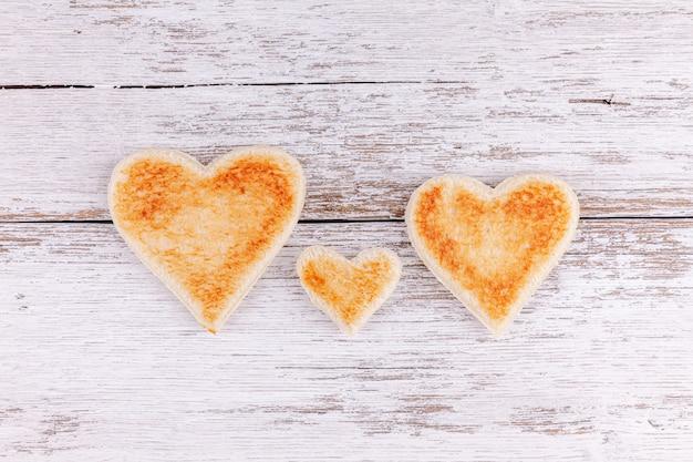 Coeurs de pain grillé sur table en bois, soutien en famille heureuse