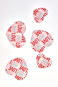 Coeurs de papier avec amour de texte, vue de dessus. fond blanc avec des coeurs en papier décoratif.