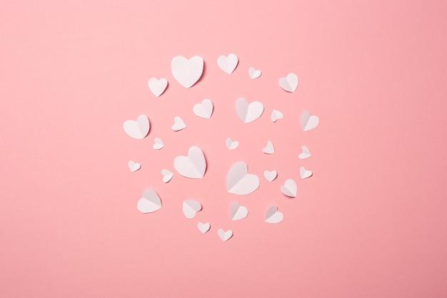 Coeurs de papier blanc sur fond rose. composition de la saint-valentin. bannière. mise à plat, vue de dessus.