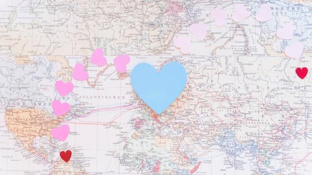 Coeurs de papier coloré sur la carte du monde