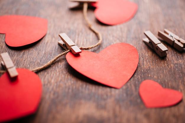 Coeurs de papier épinglé à la corde sur une table en bois