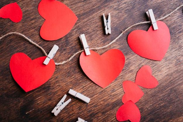 Coeurs de papier épinglés à la corde sur une table marron