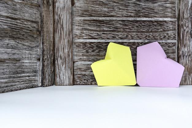 Des coeurs de papier lilas et jaune sont sur le fond d'une planche de bois sombre