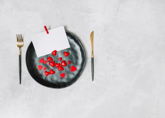 Coeurs de papier et d'ornement sur une assiette près de la coutellerie