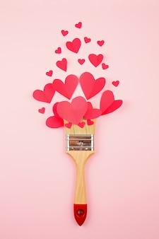 Coeurs en papier et pinceau sur le fond pastel rose.