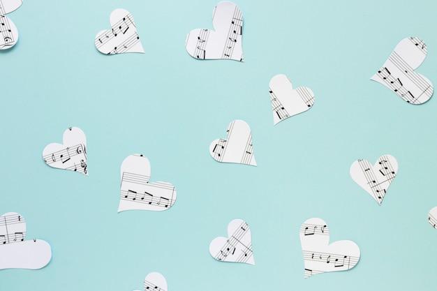 Coeurs de papier plat laïcs sur fond bleu