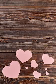 Coeurs de papier pour bannière et espace de copie. découpes décoratives en forme de coeur de papier sur fond en bois brun, vue de dessus.