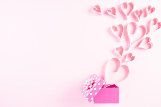Coeurs en papier rose éclaboussent de boîte-cadeau sur fond de papier pastel rose
