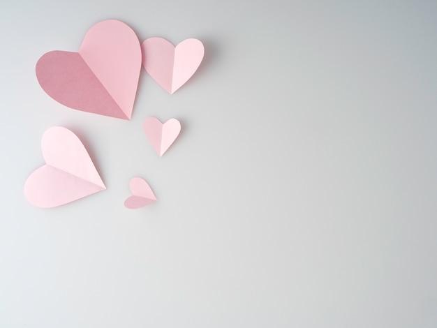 Coeurs de papier rose placés sur fond blanc.
